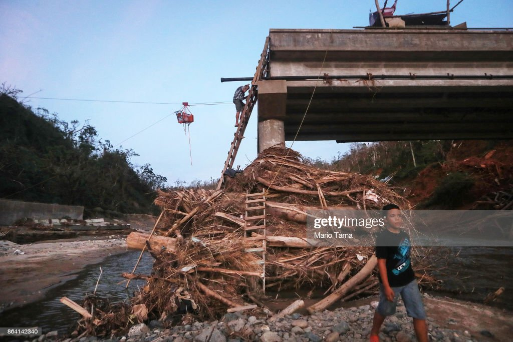 A man descends a makeshift ladder reaching to the top of a broken bridge spanning the Vivi River on October 20, 2017 in Utuado, Puerto Rico. The bridge was washed away during Hurricane Maria and makeshift ladders are the only way for members of the cut-off Rio Abajo community to access the rest of Utuado municipality. Residents cannot wade across the river because it is contaminated with human waste after a sewer pipe broke during the storm. Residents have rigged up a system of pulleys to manuever supplies across the river to their community. The 27 families in the community have no grid electricity or running water. Today is the one month anniversary of Hurricane Maria.