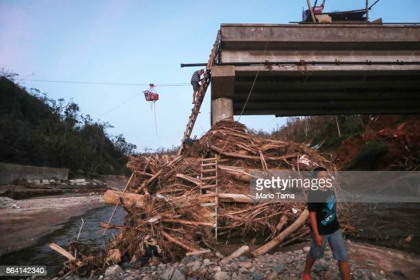 A man descends a makeshift ladder reaching to the top of a broken bridge spanning the Vivi River on October 20 2017 in Utuado Puerto Rico The bridge...