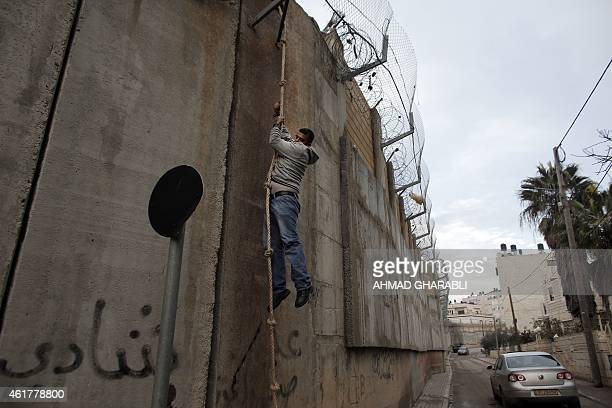 A man descends down a rope used by Palestinians to cross Israel's controversial concrete barrier that separates the West Bank from Jerusalem on...