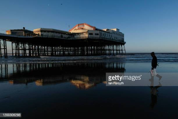 A man digging for bait walks along the beach at Blackpool on January 18 2020 in Blackpool England Warmer weather has taken over following the recent...