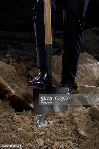 Man digging in stony ground, low section