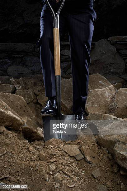 Man digging shovel into stony ground, low section