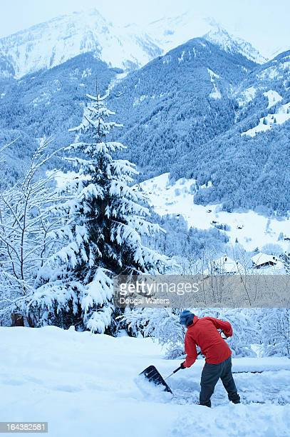 Man digging snow in Swiss Alps