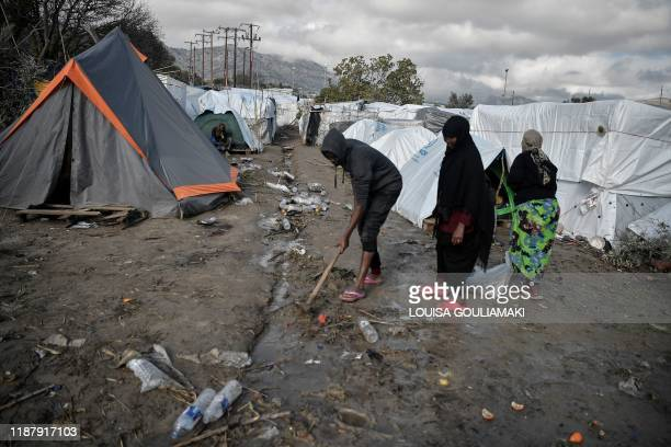 A man digs a ditch after a heavy rainfall in the makeshift migrant camp on the island of Chios on December 11 2019 where thousands of refugees and...
