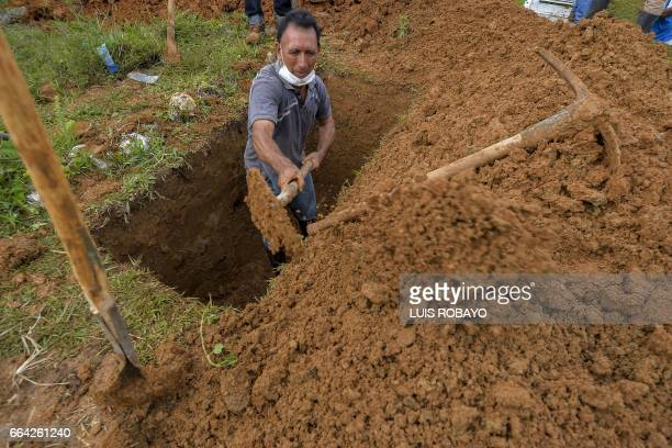 A man digs a grave of a relative killed by mudslides caused by heavy rains at the cemetery in Mocoa Putumayo department Colombia on April 3 2017...