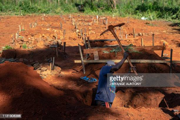 TOPSHOT A man digs a grave on March 21 2019 at the site where other Cyclone Idai victims were buried in Chimanimani as More bodies are being...