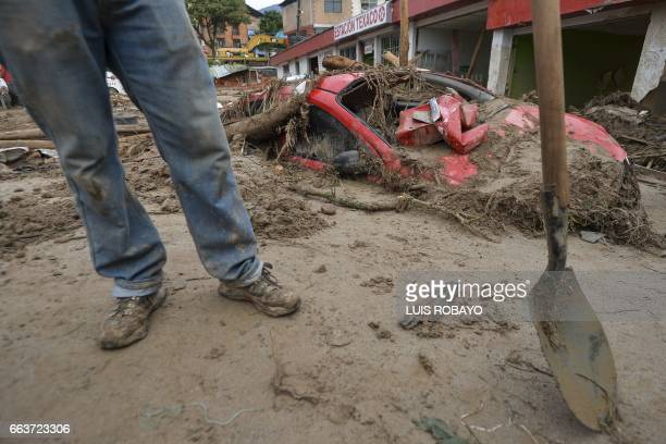 A man digs in the sludge following mudslides caused by heavy rains in Mocoa Putumayo department southern Colombia on April 2 2017 The death toll from...