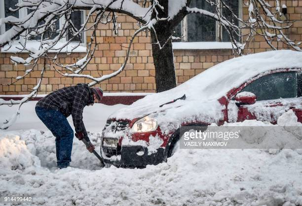 A man digs out his car after a snowstorm in Moscow on February 5 2018 Moscow authorities battled to clear streets and told children they could skip...