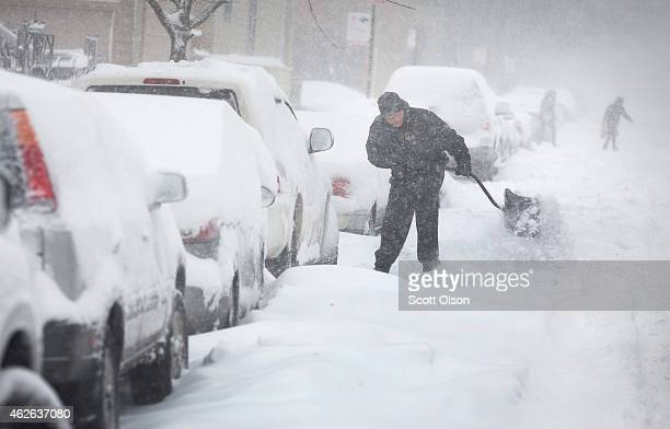 A man digs out his car along a snowcovered street on February 1 2015 in Chicago Illinois Fifteen inches or more of snow is expected to fall on the...