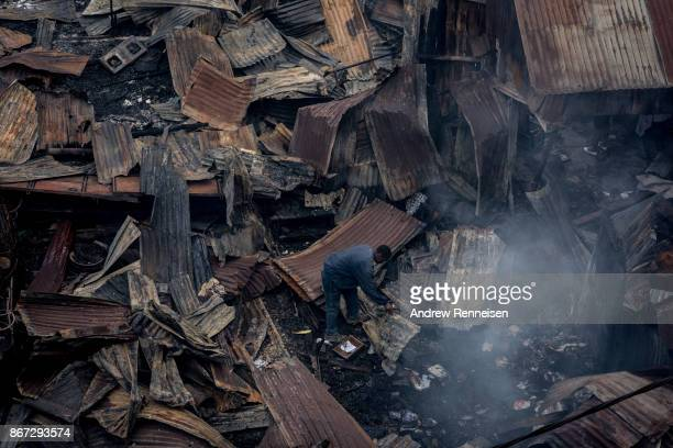 A man digs through ruins of Kikuyu homes and shops which were destroyed in the Kawangware slum on October 28 2017 in Nairobi Kenya Protests turned...