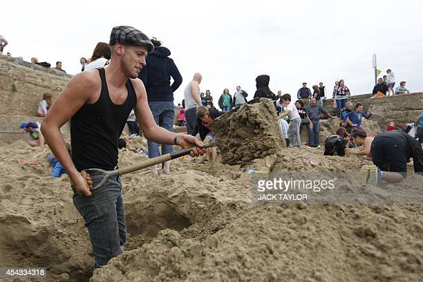 A man digs with a spade as he searches a beach in Folkestone southeast England on August 29 2014 for gold bullion buried there by German artist...