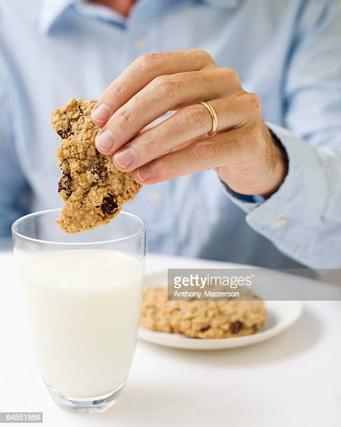 Man dipping oatmeal cookie into a glass of milk