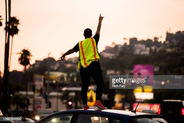 Man directs traffic at a candlelight vigil to demand justice for Elijah McClain on the one year anniversary of his death at The Laugh Factory on...