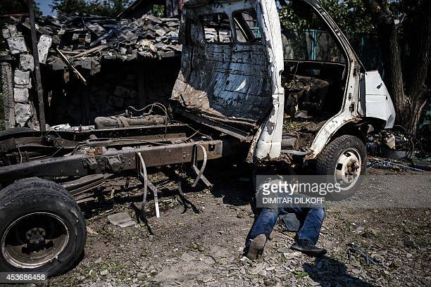 A man disassembles a car for scrap after shelling in Donetsk on August 16 2014 Diplomatic efforts to douse an international firestorm over claims...