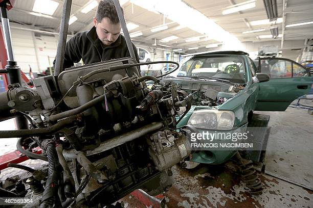 A man disassembles a used car motor at the Careco company storehouse on January 28 2015 in SaintQuentin northern France Thousands of vehicle parts...