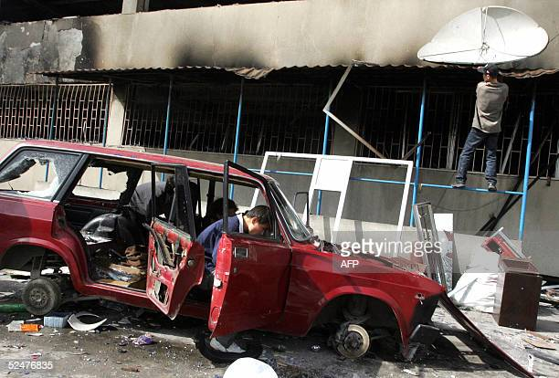 A man disassembles remains of a car as another one tries to tear away a satellite dish in front of a Chinese trading center set on fire by looters 25...