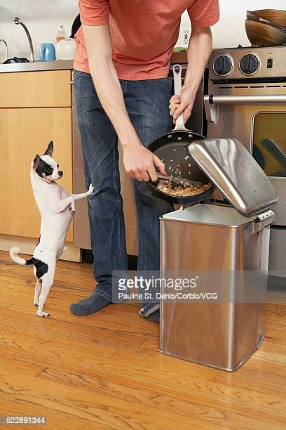 man discarding food in trash can - scraping stock photos and pictures