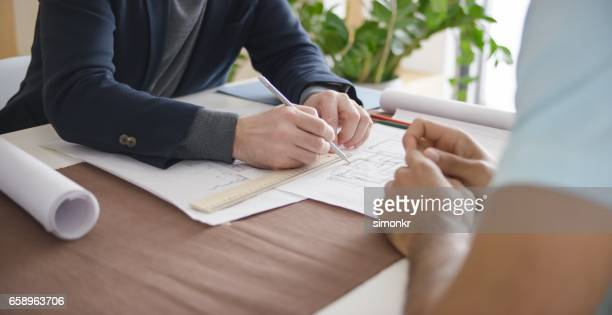 man discussing with architect - mid section stock photos and pictures