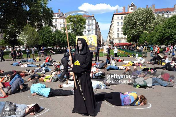 A man disguised as Grim Reaper carrying a scythe and clothed in a black cloak stands among people laying on the ground on April 23 2011 downtown Lyon...
