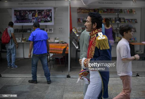 TOPSHOT A man disguised as Venezuelan liberator Simon Bolivar walks in front of book stalls during the International Book Fair of Venezuela in...