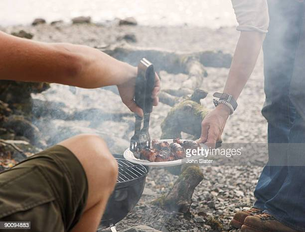 man dishing out bbq food to friend