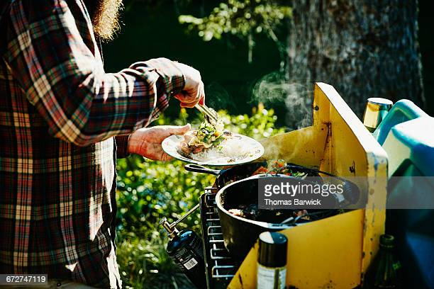 Man dishing up food for family at camp stove