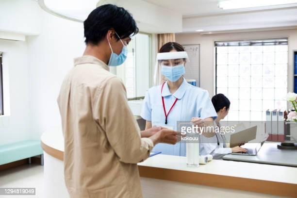 病院の受付で消毒する男性 - 消毒用アルコール ストックフォトと画像