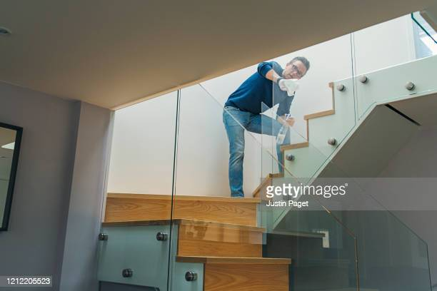 man disinfecting glass on staircase - clean stock pictures, royalty-free photos & images