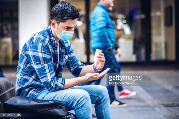 man disinfecting his hands due to coronavirus risk - hand sanitizer stock pictures, royalty-free photos & images