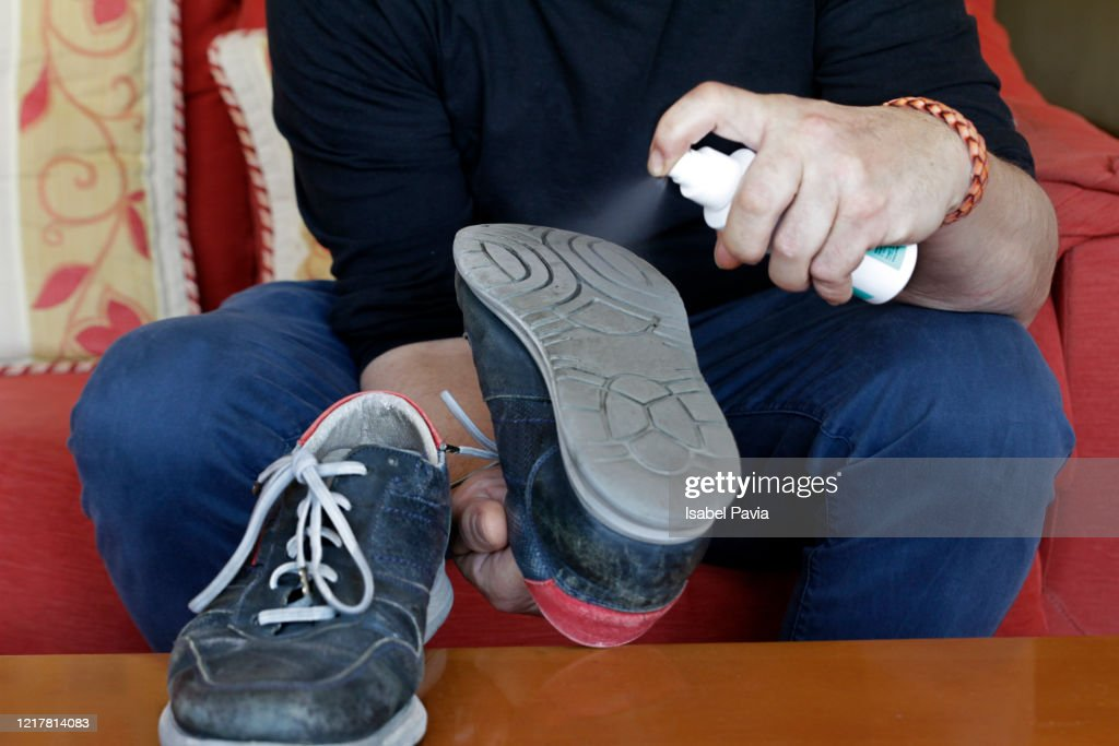 Man disinfecting shoes. Coronavirus Prevention : Stock Photo