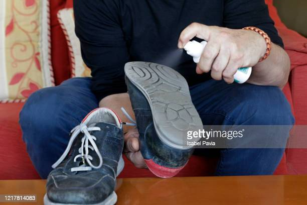 man disinfecting shoes. coronavirus prevention - 靴底 ストックフォトと画像