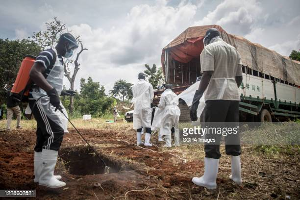 Man disinfects the earth around a grave as the burial of a coronavirus victim is carried out by the district health team in Gulu, northern Uganda....