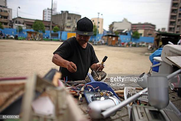 A man dismantles a television to sell the parts in the slum area of Kamagasaki on April 23 2016 in Osaka Japan Kamagasaki a district in Japan's...