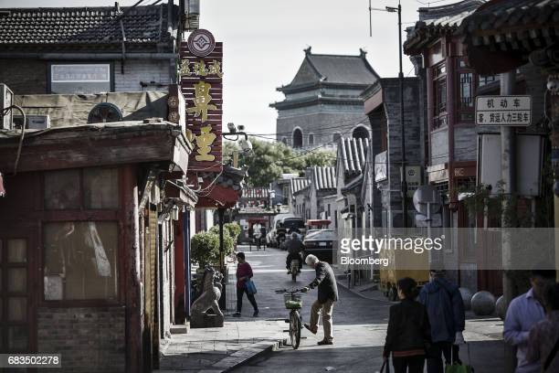 A man dismounts from a bicycle in a traditional hutong neighborhood in Beijing China on Sunday May 14 2017 Chinas economy is staging a comeback as...