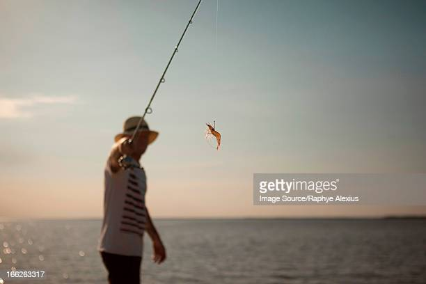 Man displaying lure on fishing line