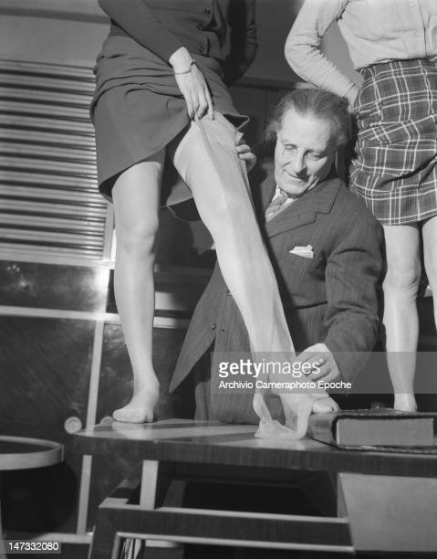 A man displaying tights on a model standing on a table Museum of Famous Tights Milan 1950