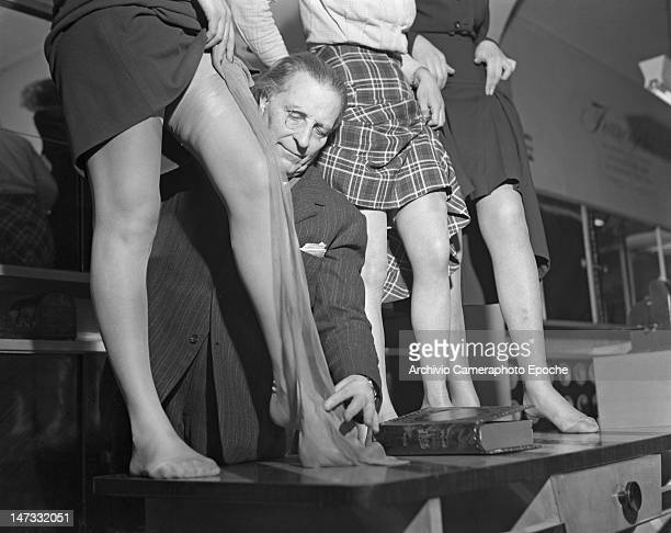 A man displaying tights on models standing on a table Museum of Famous Tights Milan 1950