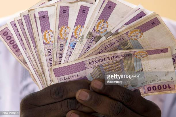 A man displays 10000 denomination Central African franc banknotes in this arranged photograph in N'Djamena Chad on Wednesday Aug 16 2017 African...