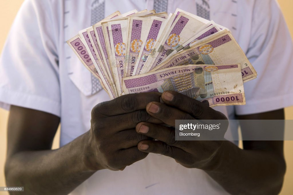 A man displays 10,000 denomination Central African franc banknotes in this arranged photograph in N'Djamena, Chad, on Wednesday, Aug. 16, 2017. African Development Bank and nations signed agreement to finance a project linking the town of Ngouandere in Cameroon and Chads capital, NDjamena, according to statement handed to reporters in Cameroonian capital, Yaounde in July. Photographer: Xaume Olleros/Bloomberg via Getty Images