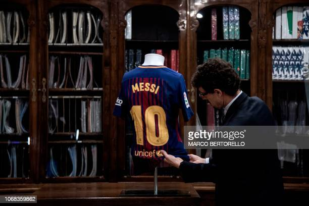 TOPSHOT A man displays a FC Barcelona football jersey worn by Argentina's player Lionel Messi during the 20172018 season from the collection Football...