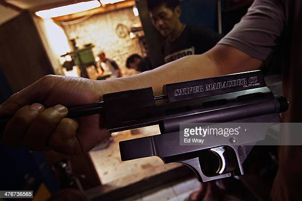 A man displays a finished trigger assembly at a small air rifle factory on March 4 2014 in Cipacing Indonesia The small village is known for its...