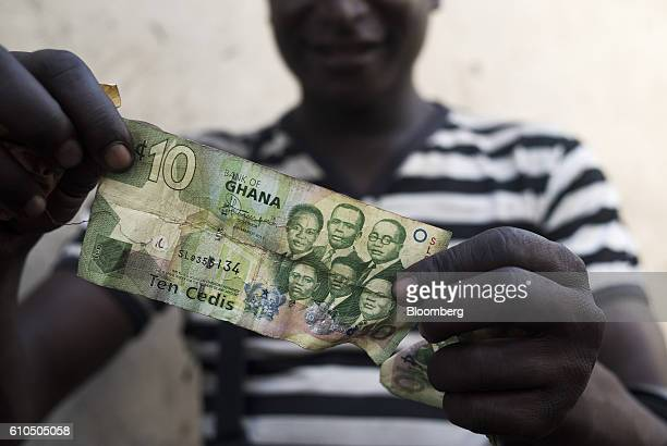 A man displays a Ghana ten cedi banknote in Accra Ghana on Sunday Sept 18 2016 Ghana's central bank expects mergers and acquisitions among lenders to...