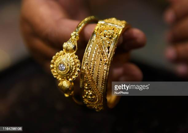 A man displays a gold jewellery bangles to the customer at a Jewellery shop in Kolkata India 26 August 2019 Gold price hits a new record high of Rs...