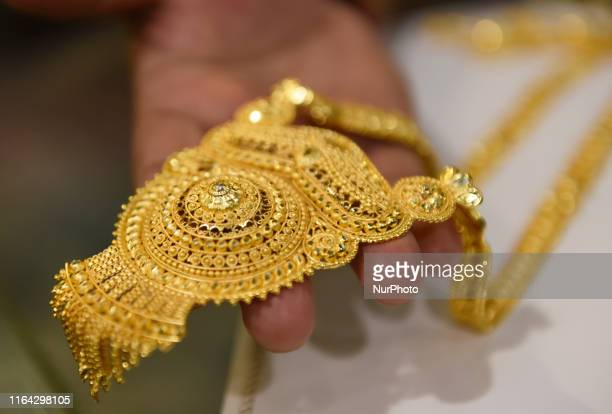 A man displays a gold necklace to the customer at a Jewellery shop in Kolkata India 26 August 2019 Gold price hits a new record high of Rs 40000 on...