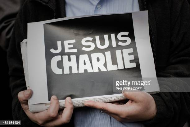 A man displays a placard in solidarity with the victims of the shooting at the Paris office of the satirical newspaper Charlie Hebdo by three gunman...