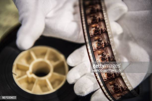 A man displays a rare cut from the film The Shining from the collection Cinema Stanley Kubrick at the Aste Bolaffi auction house in Turin on March 23...