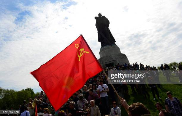 A man displays a Soviet flag in front of the Soviet soldier monument at the Soviet War Memorial in Berlin's Treptow district on May 9 as crowds...