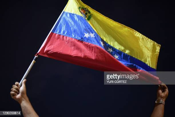 Man displays a Venezuelan flag as relatives and friends of 28 Venezuelan migrants who died when a boat transporting them to Trinidad and Tobago sank,...
