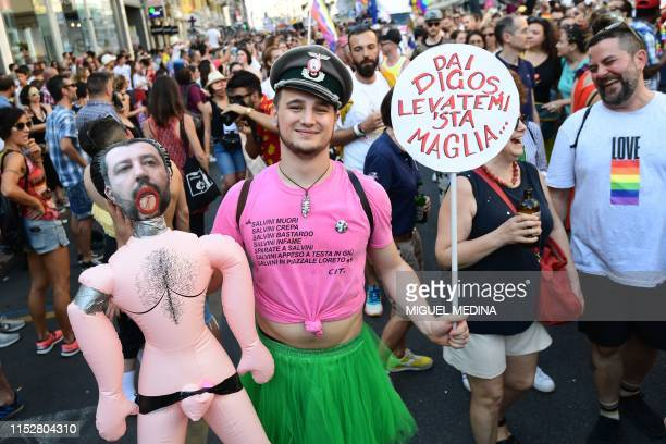 Man displays an inflatable doll with the effigy of Italy's Interior minister as people parade during the Milan Pride 2019 on June 29, 2019 in Milan,...