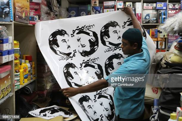 A man displays car stickers portraying Qatar's Emir Sheikh Tamim bin Hamad AlThani at a shop in the capital Doha on June 11 2017 The diplomatic...